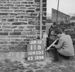 SD950111B, Man marking Ordnance Survey minor control revision point with an arrow in 1950s