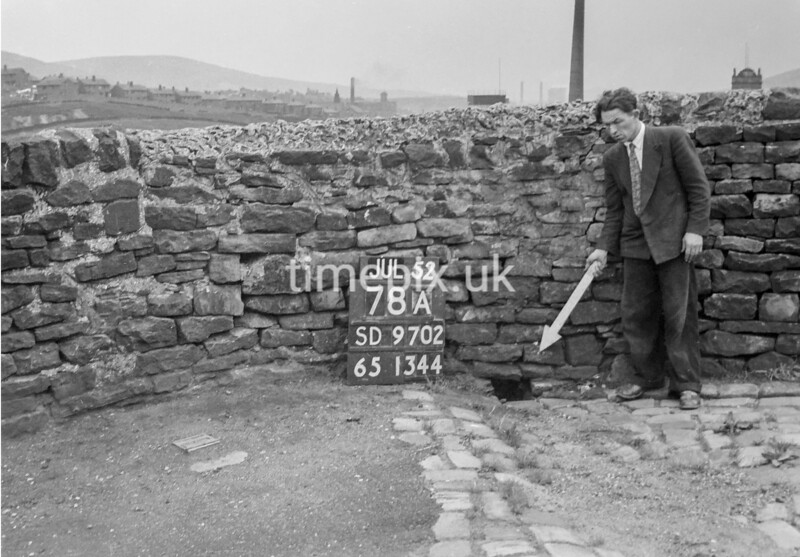 SD970278A, Man marking Ordnance Survey minor control revision point with an arrow in 1950s