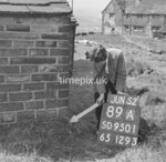 SD950189A, Man marking Ordnance Survey minor control revision point with an arrow in 1950s