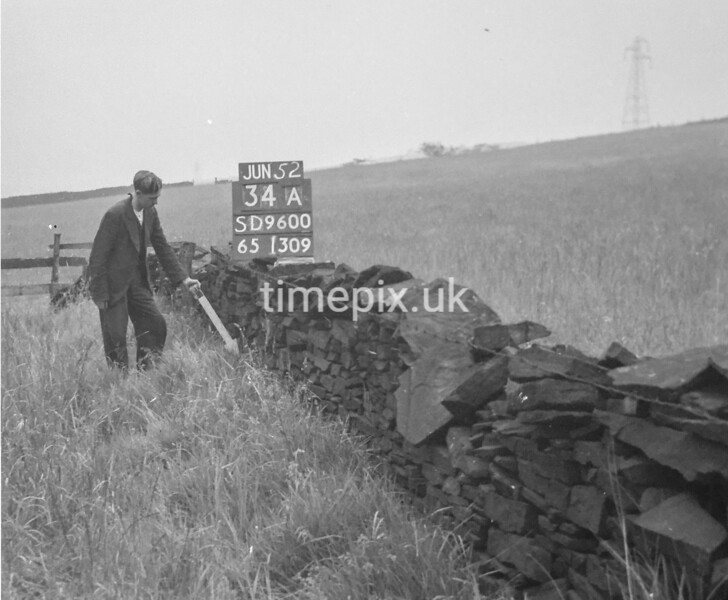 SD960034A, Man marking Ordnance Survey minor control revision point with an arrow in 1950s