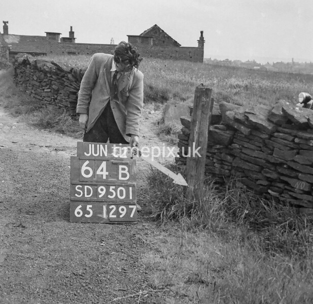 SD950164B, Man marking Ordnance Survey minor control revision point with an arrow in 1950s