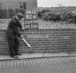 SD950082A, Man marking Ordnance Survey minor control revision point with an arrow in 1950s