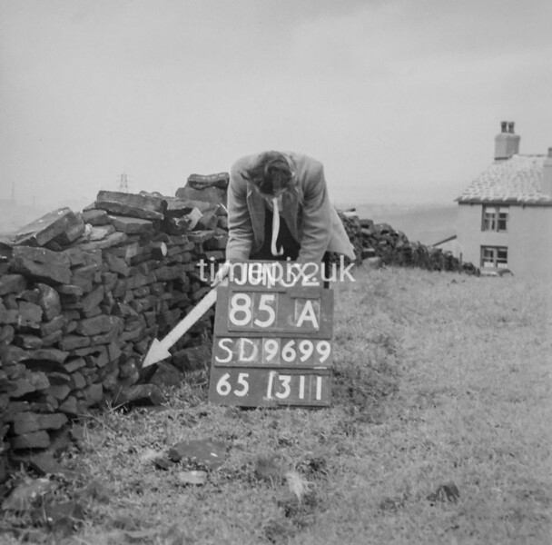 SD960085A, Man marking Ordnance Survey minor control revision point with an arrow in 1950s