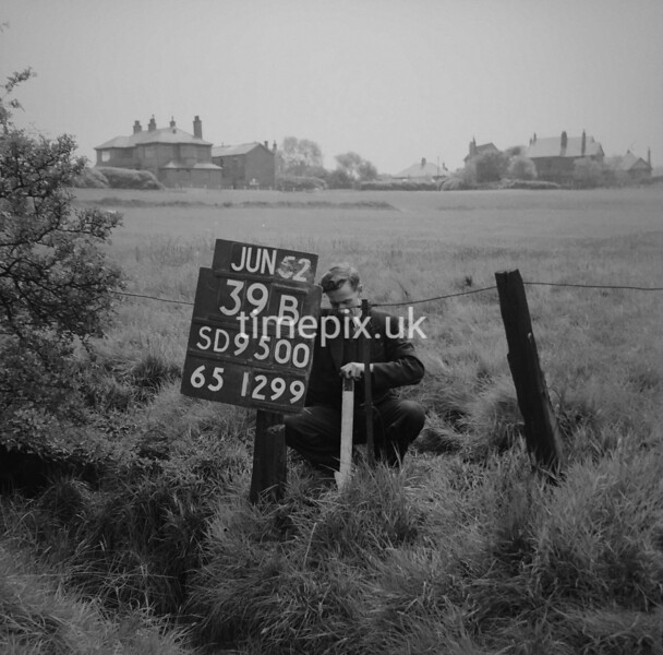 SD950039B, Man marking Ordnance Survey minor control revision point with an arrow in 1950s