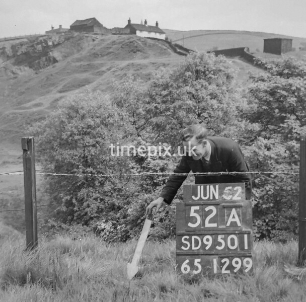 SD950152A, Man marking Ordnance Survey minor control revision point with an arrow in 1950s