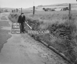 SD960014A, Man marking Ordnance Survey minor control revision point with an arrow in 1950s