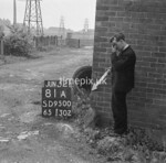 SD950081A, Man marking Ordnance Survey minor control revision point with an arrow in 1950s