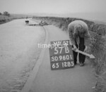 SD960157B, Man marking Ordnance Survey minor control revision point with an arrow in 1950s