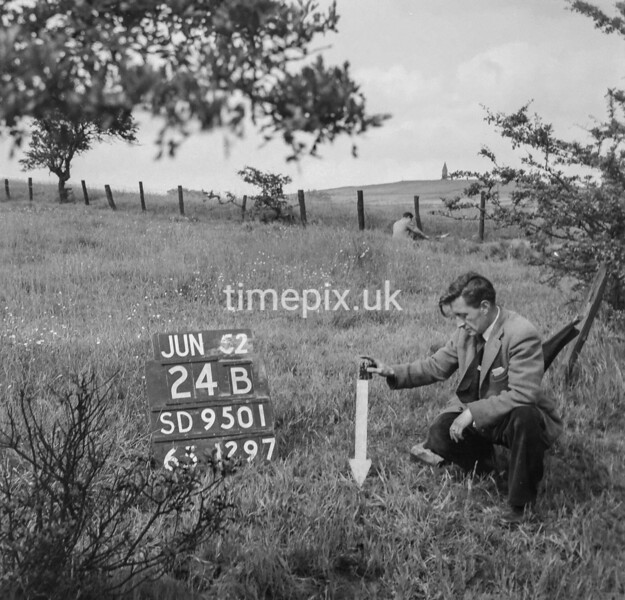 SD950124B, Man marking Ordnance Survey minor control revision point with an arrow in 1950s