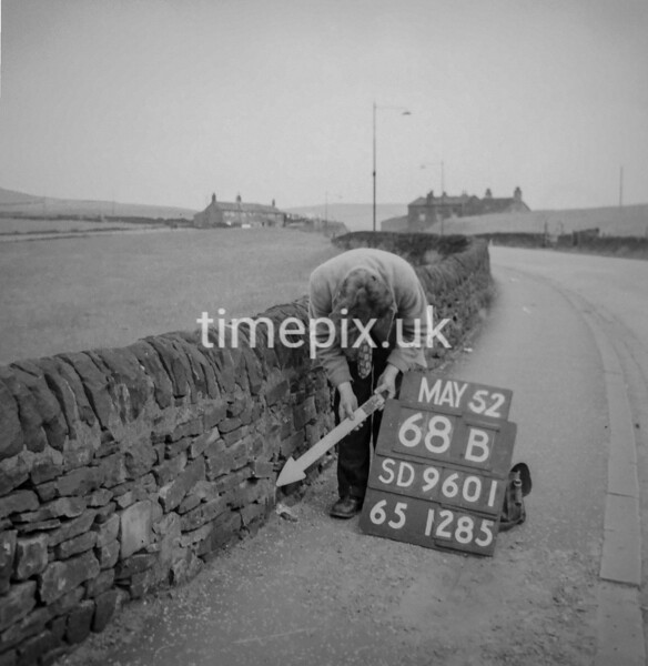 SD960168B, Man marking Ordnance Survey minor control revision point with an arrow in 1950s