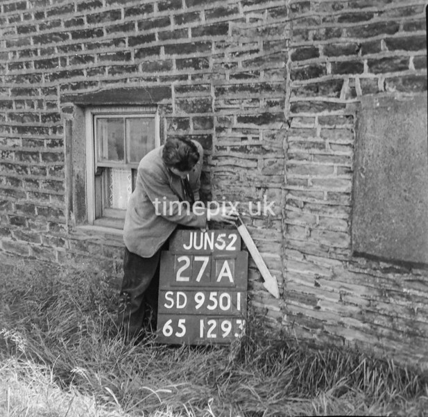 SD950127A, Man marking Ordnance Survey minor control revision point with an arrow in 1950s