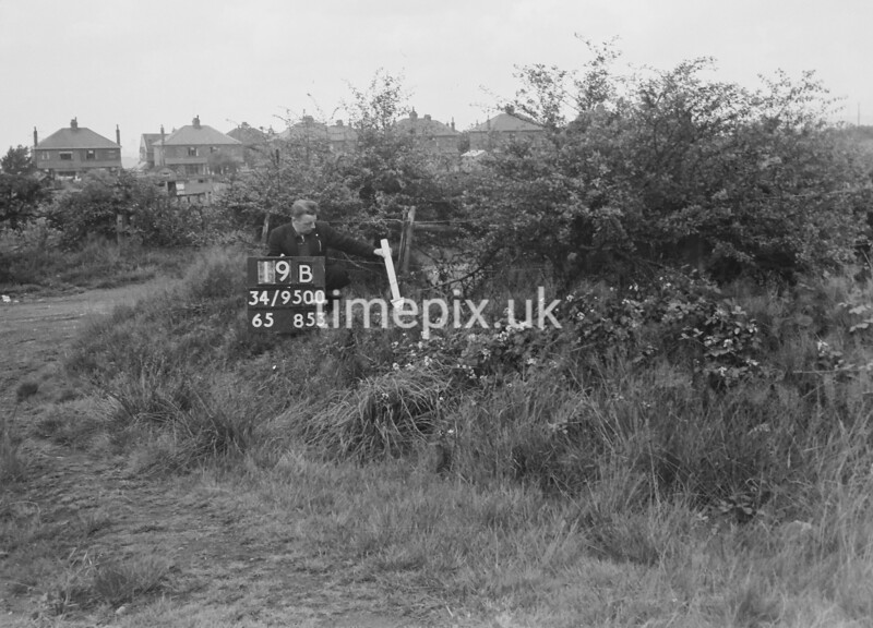 SD950019B, Man marking Ordnance Survey minor control revision point with an arrow in 1950s