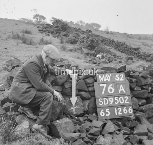 SD950276A, Man marking Ordnance Survey minor control revision point with an arrow in 1950s