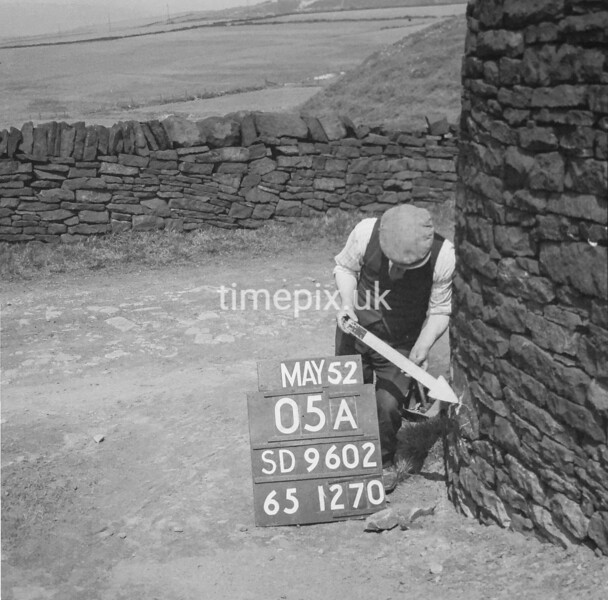 SD960205A, Man marking Ordnance Survey minor control revision point with an arrow in 1950s