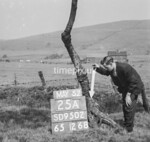SD950225A, Man marking Ordnance Survey minor control revision point with an arrow in 1950s
