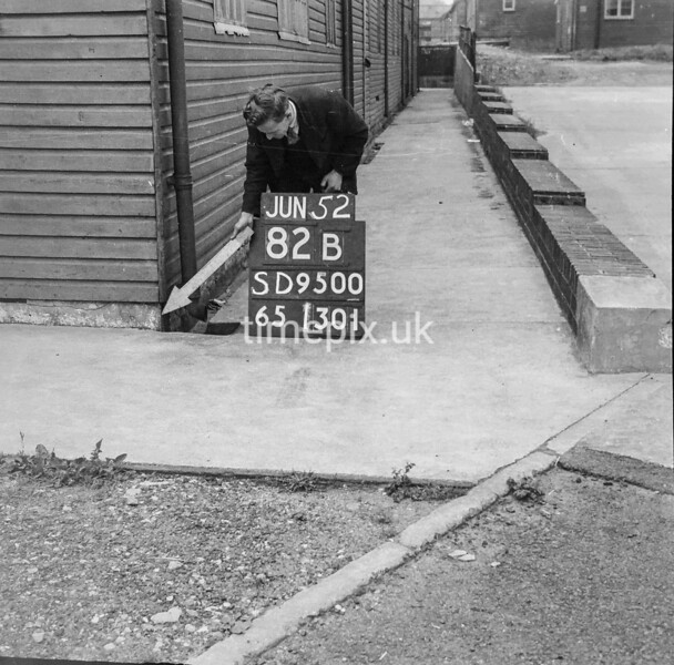 SD950082B, Man marking Ordnance Survey minor control revision point with an arrow in 1950s