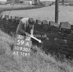 SD950159A, Man marking Ordnance Survey minor control revision point with an arrow in 1950s