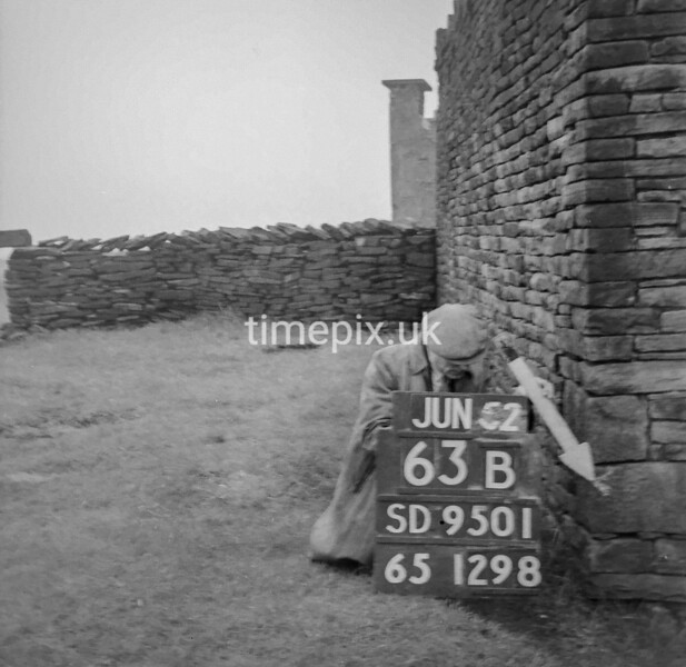 SD950163B, Man marking Ordnance Survey minor control revision point with an arrow in 1950s