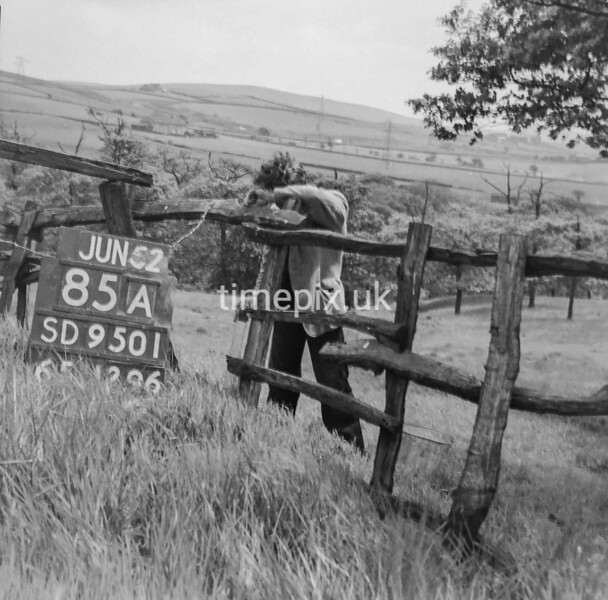 SD950185A, Man marking Ordnance Survey minor control revision point with an arrow in 1950s