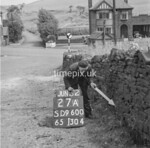 SD960027A, Man marking Ordnance Survey minor control revision point with an arrow in 1950s