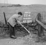 SD950122A, Man marking Ordnance Survey minor control revision point with an arrow in 1950s