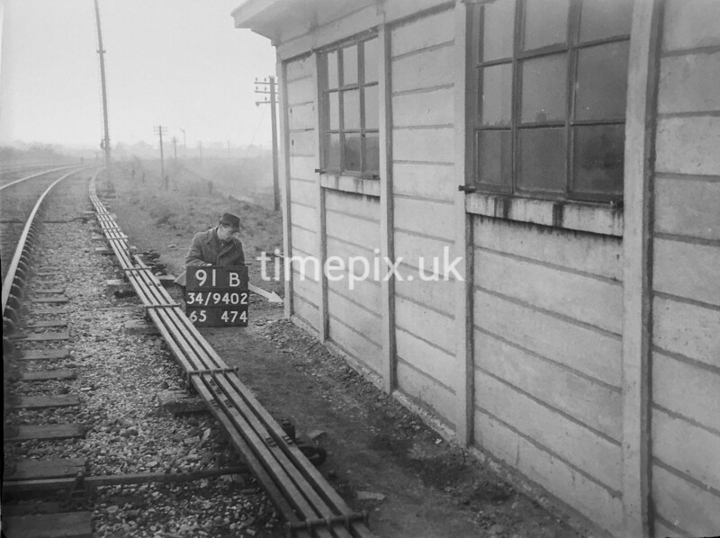 SD940291B, Man marking Ordnance Survey minor control revision point with an arrow in 1950s