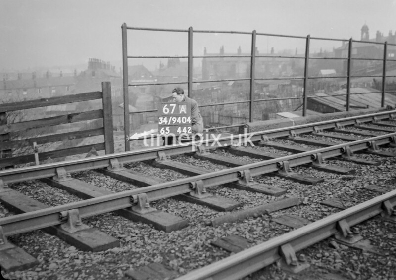 SD940467A, Man marking Ordnance Survey minor control revision point with an arrow in 1950s