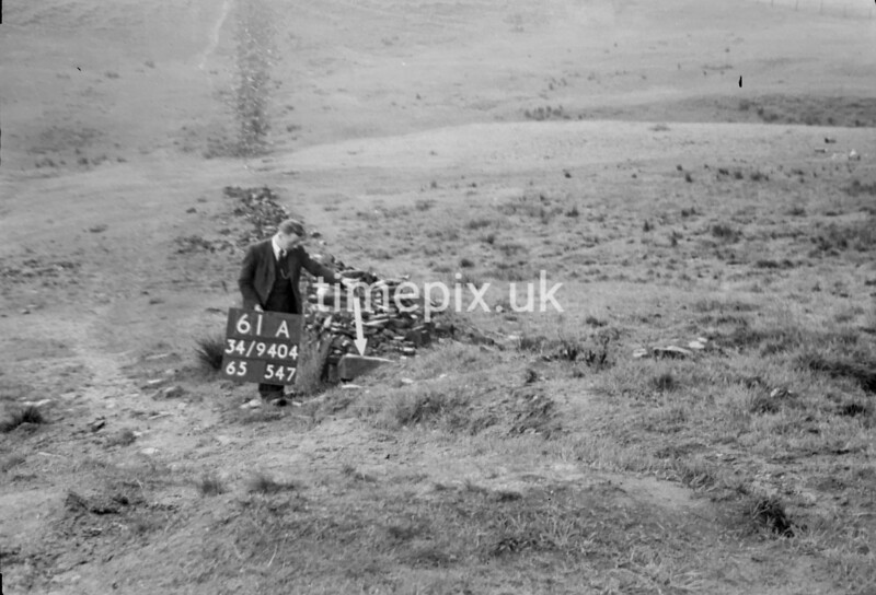 SD940461A, Man marking Ordnance Survey minor control revision point with an arrow in 1950s