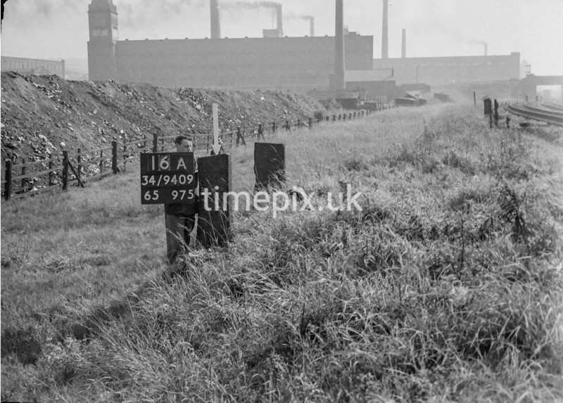 SD940916A, Man marking Ordnance Survey minor control revision point with an arrow in 1950s