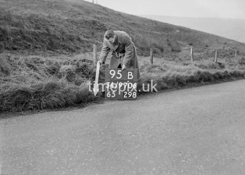 SD970695B, Man marking Ordnance Survey minor control revision point with an arrow in 1950s