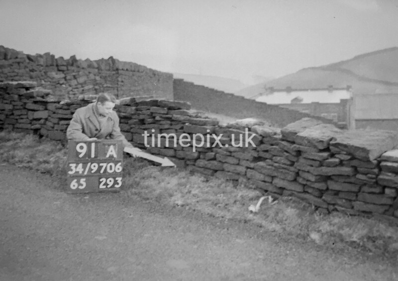 SD970691A, Man marking Ordnance Survey minor control revision point with an arrow in 1950s