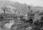 SD970861A, Man marking Ordnance Survey minor control revision point with an arrow in 1950s
