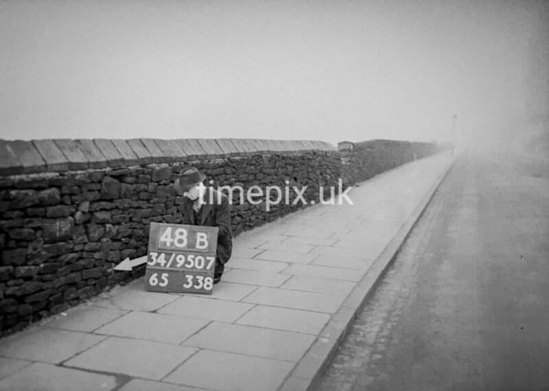 SD950748B, Man marking Ordnance Survey minor control revision point with an arrow in 1950s