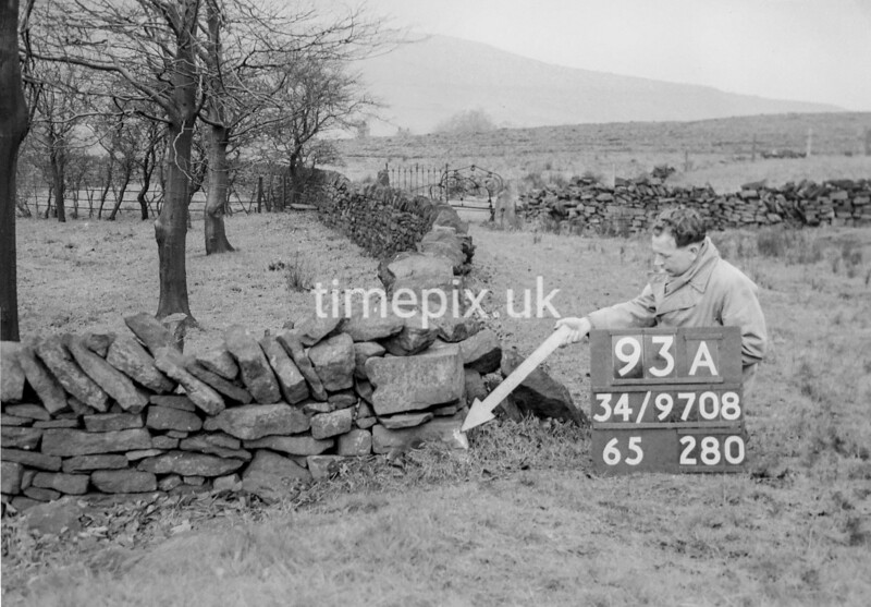 SD970893A, Man marking Ordnance Survey minor control revision point with an arrow in 1950s
