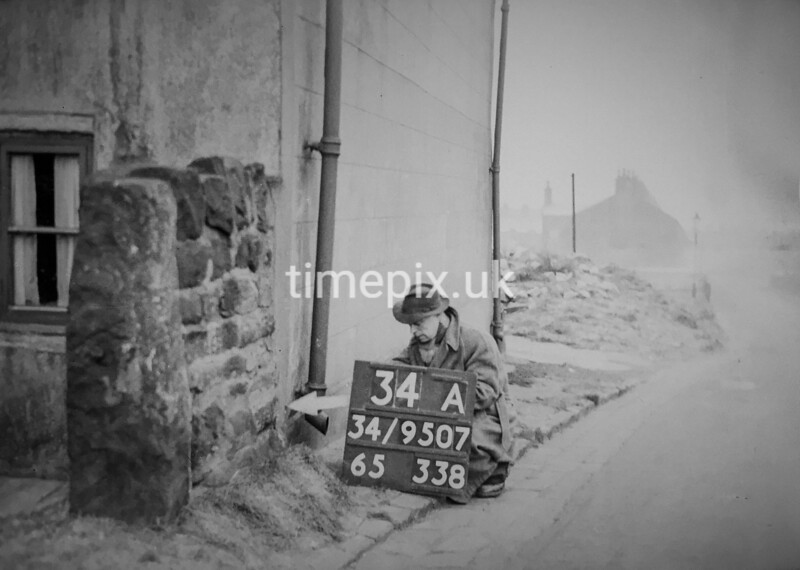 SD950734A, Man marking Ordnance Survey minor control revision point with an arrow in 1950s