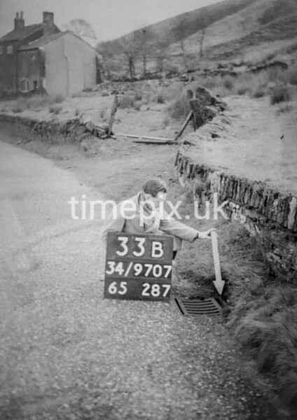 SD970733B, Man marking Ordnance Survey minor control revision point with an arrow in 1950s