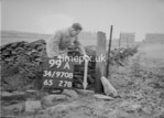 SD970899A, Man marking Ordnance Survey minor control revision point with an arrow in 1950s