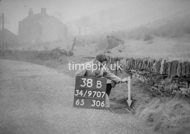 SD970738B, Man marking Ordnance Survey minor control revision point with an arrow in 1950s
