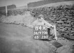 SD970884A, Man marking Ordnance Survey minor control revision point with an arrow in 1950s