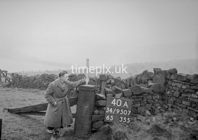 SD950740A, Man marking Ordnance Survey minor control revision point with an arrow in 1950s