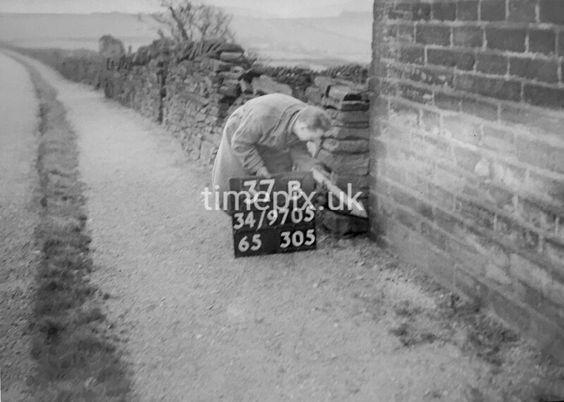 SD970537B, Man marking Ordnance Survey minor control revision point with an arrow in 1950s