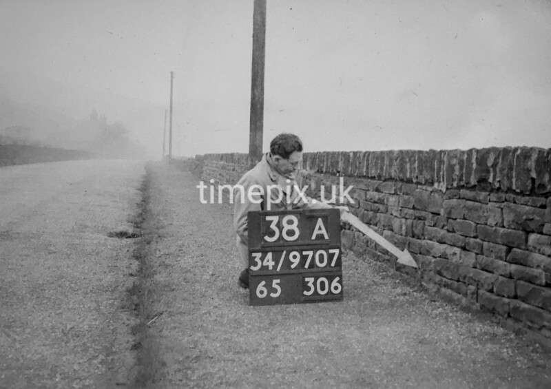 SD970738A, Man marking Ordnance Survey minor control revision point with an arrow in 1950s