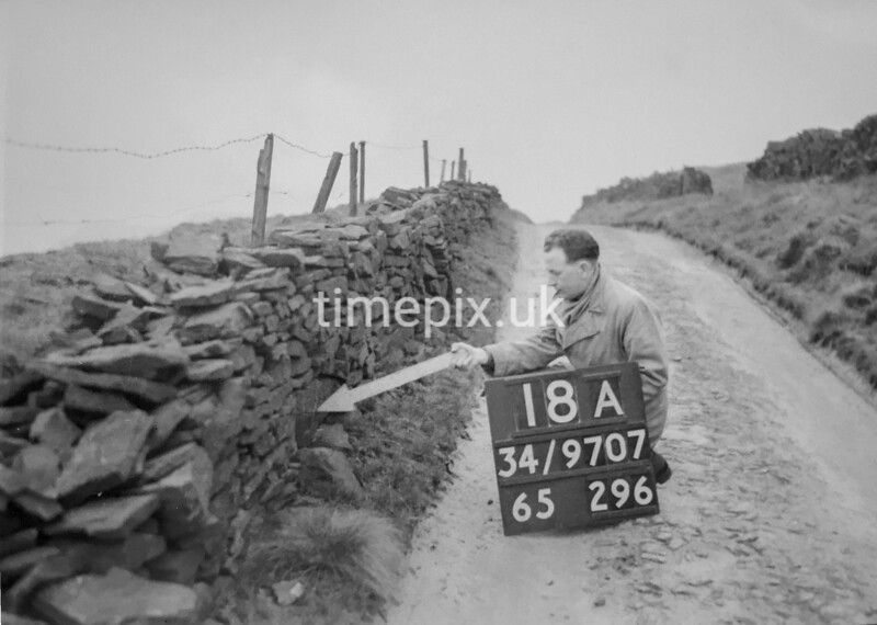 SD970718A, Man marking Ordnance Survey minor control revision point with an arrow in 1950s