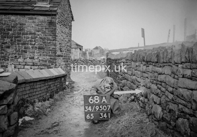 SD950768A, Man marking Ordnance Survey minor control revision point with an arrow in 1950s