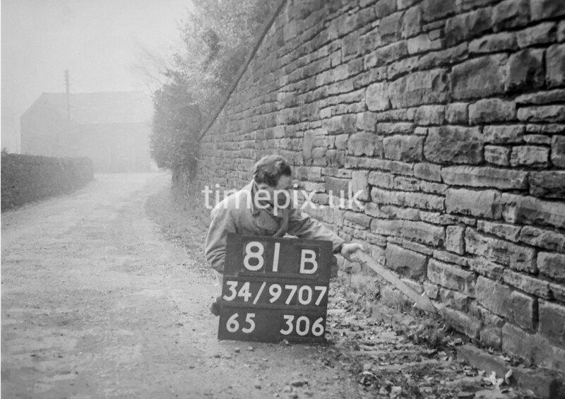 SD970781B, Man marking Ordnance Survey minor control revision point with an arrow in 1950s