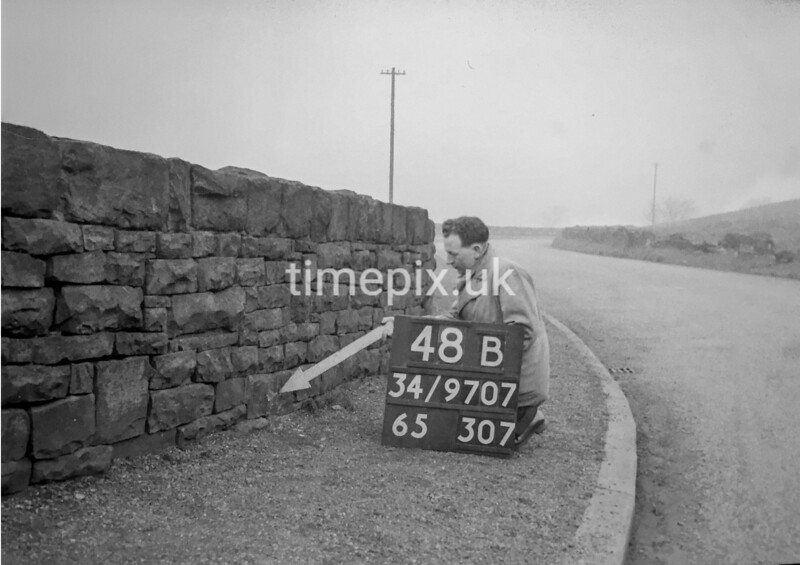 SD970748B, Man marking Ordnance Survey minor control revision point with an arrow in 1950s