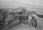 SD970866K, Man marking Ordnance Survey minor control revision point with an arrow in 1950s