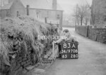 SD970883A, Man marking Ordnance Survey minor control revision point with an arrow in 1950s