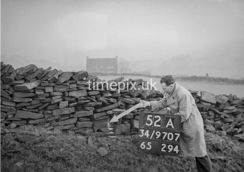 SD970752A, Man marking Ordnance Survey minor control revision point with an arrow in 1950s