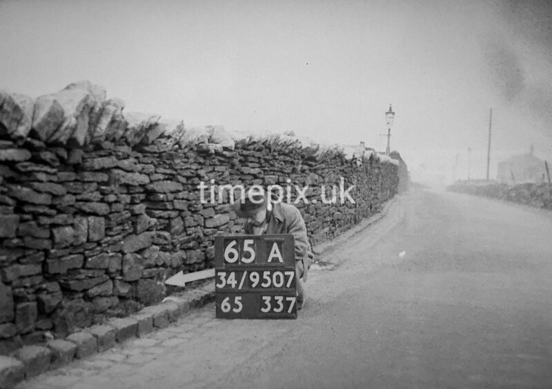 SD950765A, Man marking Ordnance Survey minor control revision point with an arrow in 1950s
